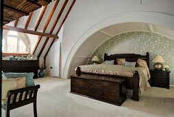 Double bed with dark brown wooden frame in niche formed by arch of vault in converted church interior