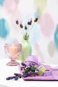 Sprigs of lavender, ribbon and washi tape in front of candle and vase of lavender