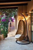 Wicker hanging chair on Mediterranean terrace covered in bougainvillea