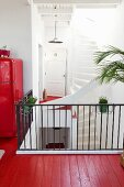 Red-painted wooden floor and black metal stair rail on gallery in open-plan stairwell