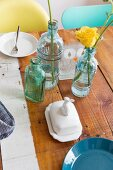 Flowers in retro glass bottles and crockery on wooden table