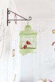 Metal bird ornaments in green vintage birdcage hanging from metal wall bracket
