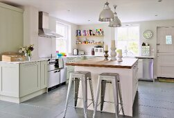 Retro, metal bar stools at free-standing island counter in open-plan, country-house kitchen