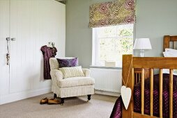 Foot of bed, pale grey armchair and white wardrobe in corner of pale-grey bedroom with patterned roller blind on window