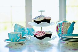 Pale blue tea set and cupcakes on cake stand on table