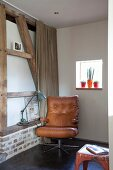 Brown leather armchair in corner and retro table lamp on masonry shelf in half-timbered wall