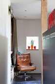 Brown leather armchair and retro table lamp in corner below window