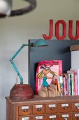 Turquoise, vintage table lamp, books and modern, colourful drawing on top of vintage apothecary cabinet