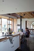 Open-plan kitchen in renovated country house with modern counter and man in dining area