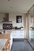 Open-plan kitchen with modern, white kitchen counter and blue. vintage advertising sign in renovated country house belonging to artist