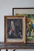 Frames Renaissance portrait of man and vintage film posters on rustic wooden bench