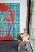 Books on wooden stool in front of large, modern portrait of man in artist's studio