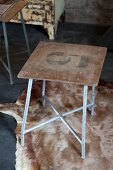 Vintage stool with number on simple wooden seat and metal frame on animal-skin rug