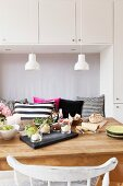 Dining table below row of pendant lamps with white ceramic lampshades