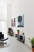 Living area with sideboards against wall below large portraits in loft apartment