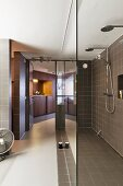 Designer bathroom with glass partition in front of brown-tiled shower area