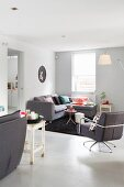 Grey swivel armchair and corner couch in lounge area with designer standard lamp