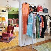Retro women's clothing hanging on clothes rack next to open door with view into feminine bedroom