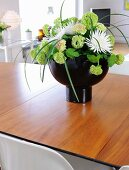 Hydrangeas and white dahlias in black designer vase on wooden table