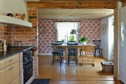 Kitchen counter next to wide open doorway with view of dining area in rustic house