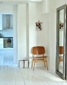 Hallway with minimalist furnishings with full-length mirror and wooden chair on white wooden floor