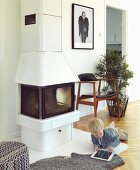 White wood-burning stove and classic chair in renovated, Scandinavian country house with herringbone parquet floor; little boy playing with tablet PC on floor