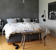 Double bed against grey wall, natural wooden floor and rustic bench in bedroom