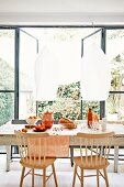 Simple wooden chairs around fruit and bread on table below pendant lamps with white lampshades; open terrace doors with view into garden