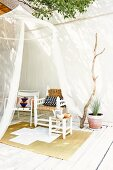 Translucent mosquito net hanging from tree, stool, various chairs and sisal rug on white-painted wooden terrace