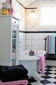 Free-standing bathtub with lit candle on bath rack in black and white country-house bathroom