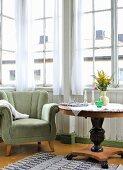 Velvet armchair and flowers on round Biedermeier table in vintage-style window bay