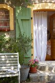 Granite steps, a bench and an olive tree in front of a door with shutters and a curtain in a French country house