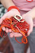 Red and orange bead necklaces held in woman's hands