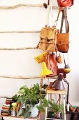 Leather bags hanging on rack made from branches above potted plants and desk lamps on stools