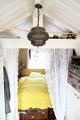 Cubby bed behind lace curtain, Oriental pendant lamp and storage in vintage suitcases