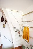 Oriental lanterns on narrow staircase and DIY clothes rack made of branches