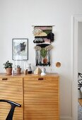 Hand-woven, decorative wall-hanging above sideboard