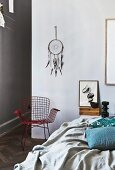 Hand-crafted dreamcatcher above wire armchair; bed with throw and scatter cushions in foreground