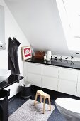 Modern, white bathroom with fitted cabinets under sloping ceiling with bird wall stickers and black accessories