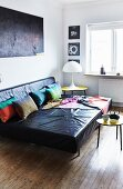 Large, black leather sofa with colourful scatter cushions and blanket, small, yellow retro table and white table lamp in living room