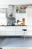 Utensils and wall cabinets in white fitted kitchen with retro barstool