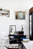 White-painted wooden chair and black shelves in vintage interior