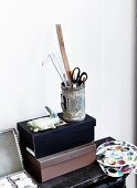 Can of drawing utensils on top of shoeboxes and painter's palettes on shelf
