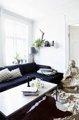 Modern coffee table, dark sofa, large Buddha statue and wooden flooring with peeling paint