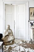 Large Buddha statue on floor with peeling paint in front of white double doors