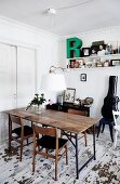 Rustic table and 60s-style wooden chairs below contemporary pendant lamp with white lampshade in dining room with distressed wooden floor