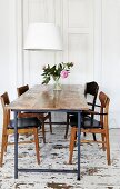 Rustic table and 60s-style chairs below contemporary pendant lamp with white lampshade in dining room with distressed wooden floor