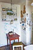 Rustic tale and stool in corner below wall-mounted plate rack in vintage interior