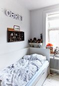 Single bed with high headboard and backrest, display case and decorative letters on wall in vintage-style interior