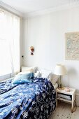 Bed with blue and white patterned bed line in corner of simple room